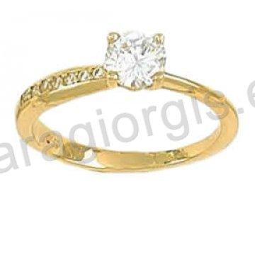 Μονόπετρο δαχτυλίδι χρυσό Κ14 με πέτρα στο κέντρο και πλαϊνές πέτρες ζιργκόν.